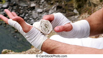 Fit man wrapping hands in bandage overlooking the ocean