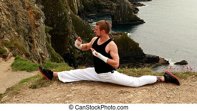 Fit man practicing martial arts overlooking the ocean