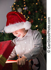 Child opening his christmas present with tree behind him