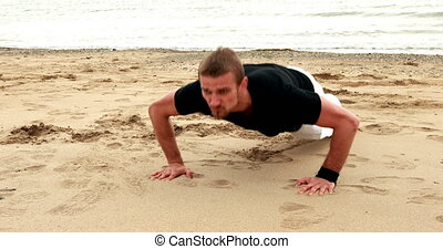 Fit man doing push ups on the beach