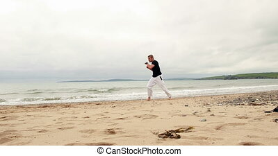 Fit man practicing martial arts on the beach