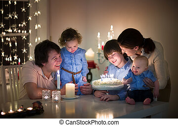 Young happy family with three kids celebration the birthday...