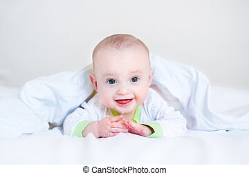Adorable funny laughing baby playing peek-a-boo