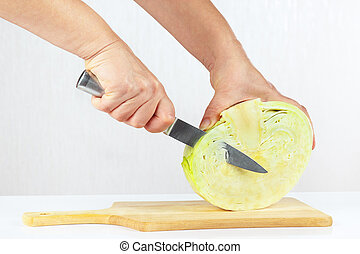 Hands with a knife shred cabbage on a cutting board close up