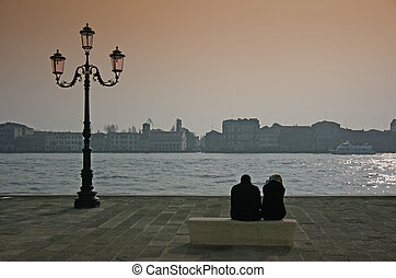 Couple in Venice sitting on a bench by the Giudecca canal