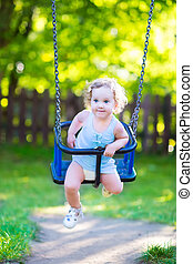 Laughing toddler girl on swing