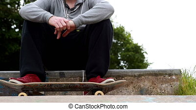 Young skateboarder sitting at the outdoor skatepark on a...