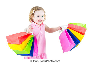 Little girl showing colorful bags - Adorable little girl...