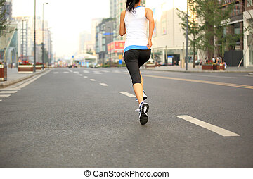 Runner athlete running on city road. woman fitness jogging...