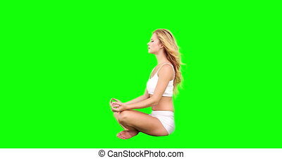 Pretty blonde sitting in lotus pose on green screen...