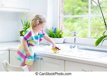 Cute curly toddler washing dishes - Cute curly toddler girl...