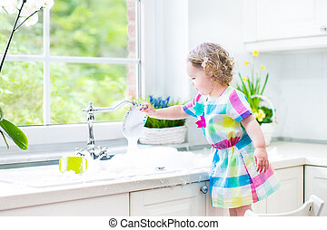 Cute toddler girl washing dishes - Cute curly toddler girl...