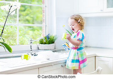 Cute curly toddler girl washing dis - Cute curly toddler...