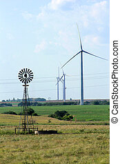 Wind Generators and Old Wind Mill on farm land with power lines