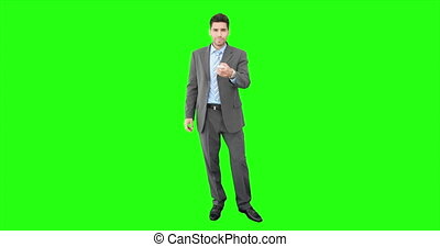 Young businessman using remote control on green screen...