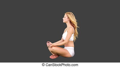 Pretty blonde sitting in lotus pose on grey screen...