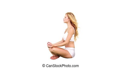 Pretty blonde sitting in lotus pose on white background