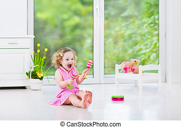 Cute curly toddler girl playing tambourine in a sunny white...