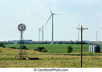 Windmill, wind turbine, powerlines and farmland - A scene of...