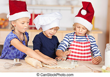 Girl Using Cookie Cutters On Dough With Sisters