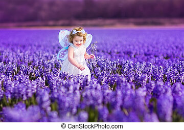 Toddler girl in fairy costume playing in a flower field -...