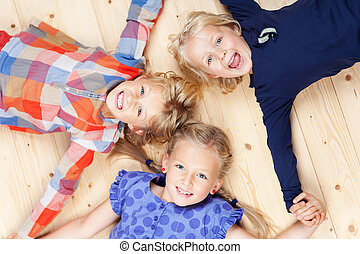 Little Siblings Lying On Hardwood Floor - High angle view of...