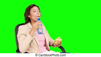 Businesswoman eating sandwich for lunch on green screen...