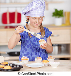Girl Garnishing Cupcakes At Kitchen Counter - Cute little...