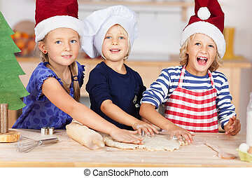 Girl Using Cookie Cutters On Dough With Sisters At Kitchen Count