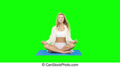 Pretty fit blonde doing yoga on green screen background