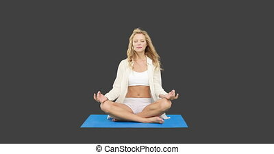 Pretty fit blonde doing yoga on grey screen background