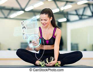 smiling woman with smartphone and earphones in gym -...