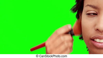 Make up artist putting powder on models face on green screen...
