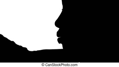 Silhouette of make up artist working on model on white...