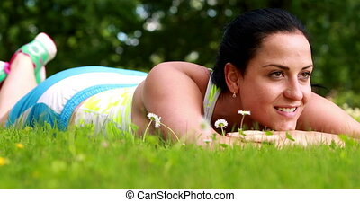 Pretty brunette lying down on the grass on a sunny day