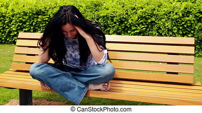 Sad brunette thinking on bench in the park on a sunny day