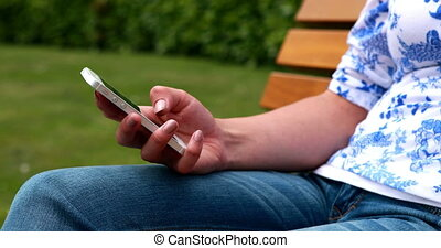 Woman sitting on park bench texting on a sunny day