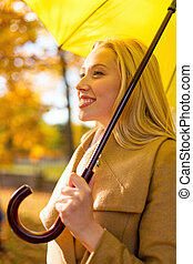 smiling woman with umbrella in autumn park - season,...