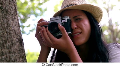 Woman using camera in the park - Woman using retro camera in...
