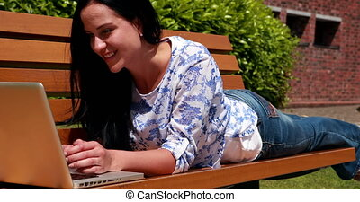 Woman lying on park bench using laptop on a sunny day