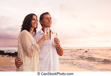 Romantic Couple Drinking Champagne on the Beach at Sunset -...
