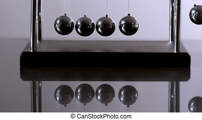 Newtons cradle in motion on reflective surface in slow...