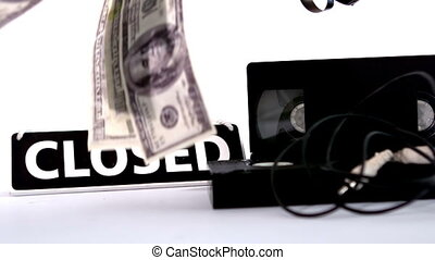 Dollars falling beside film video tapes and closed sign in...