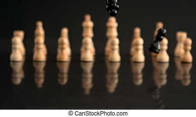 Black chess pieces falling on black background with white...
