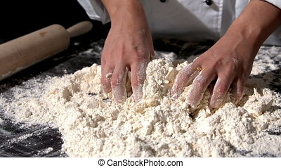 Chef kneading ingredients together to form a dough in slow...