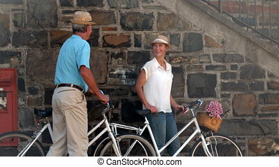 Senior couple going on a bike ride in the city in slow...