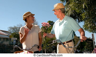Senior couple going on a bike ride in the city with man...