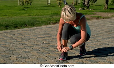 Senior woman tying her shoelace on the path in slow motion