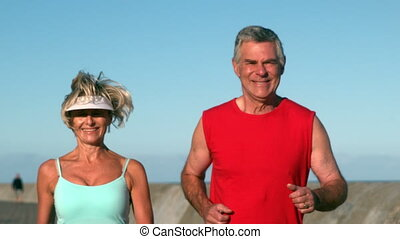 Senior couple jogging on a sunny day in slow motion