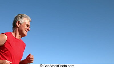 Senior man jogging on sunny day in slow motion